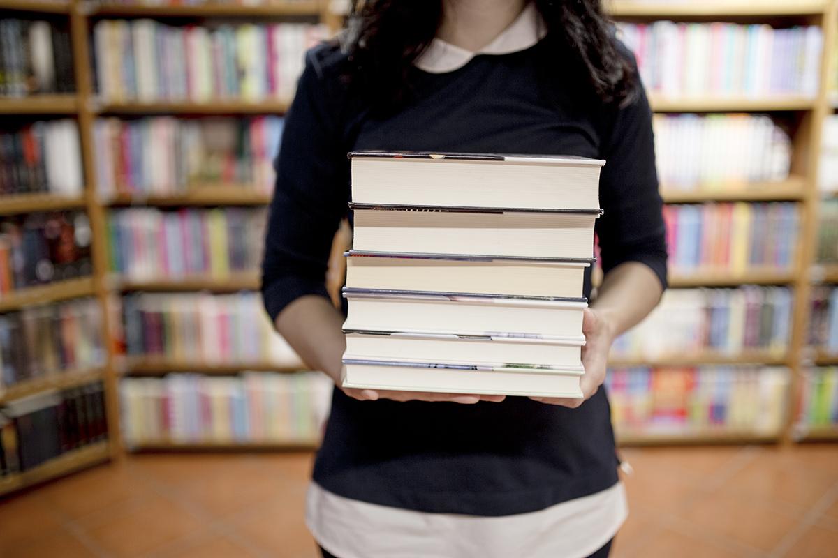 Forschung & Publikationen - Symbolfoto Frau mit Büchern